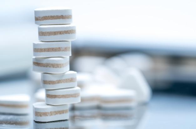 Makro pchnięciu tabletek w kształcie trójkąta. trójwarstwowe tabletki nasenne wskazujące na leki zobojętniające kwas żołądkowy, trawienny i żołądkowy