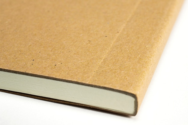Makro- pusty notatnika kąt z kartonowym hardcover odizolowywającym na bielu