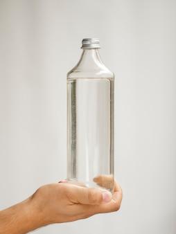Makro ręki trzymającej butelkę wody makiety
