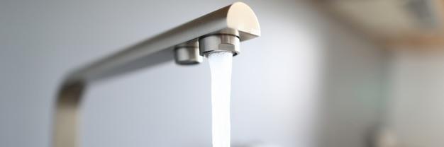 Makro strumień wody ze srebrnego kranu w kuchni