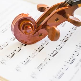 Makro- strzał drewniana skrzypcowa ślimacznica i sznurki na muzykalnych notatkach