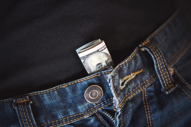 Makro strzał modnych dżinsów z amerykańskim banknotem 100 w kieszeni. bill z benjaminem franklinem złożyli i wepchnęli się w spodnie i majtki prostytutki.