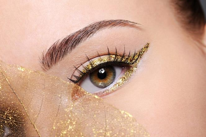 Makro strzał piękna kobiecego oka ze złotym eyeliner makijażem pokryte sztucznym żółtym liściem