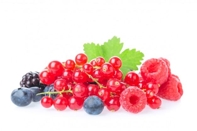 Makro strzał świeżych malin, jagód, jeżyn, czerwonych porzeczek i jeżyn z liśćmi na białym tle.