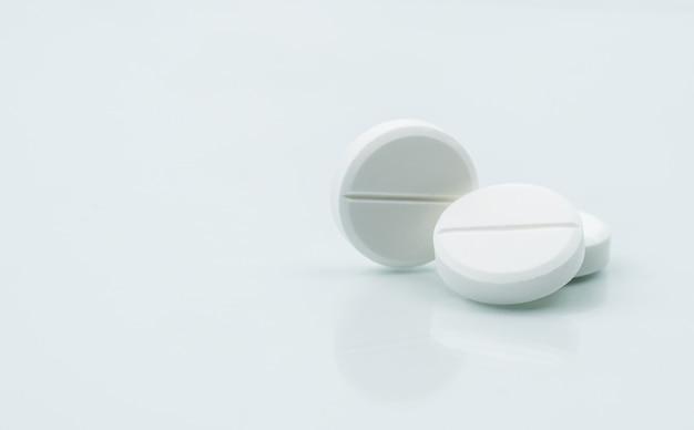 Makro strzał z trzech białych tabletek do żucia na białym tle z cieniami.