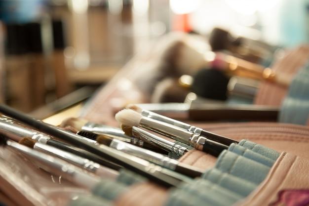 Makro, w którym wizażystka miesza kosmetyki na palecie. narzędzia do makijażu