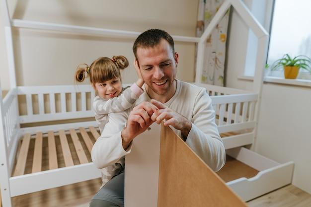 Mała 4-letnia dziewczynka pomaga ojcu w montażu lub naprawie szuflady łóżka w dziecięcej sypialni.