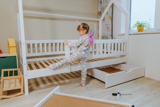 Mała 4-letnia dziewczynka ubrana w piżamę i kostium skrzydeł motyla bawi się w dziecięcej sypialni przy nowym łóżku.