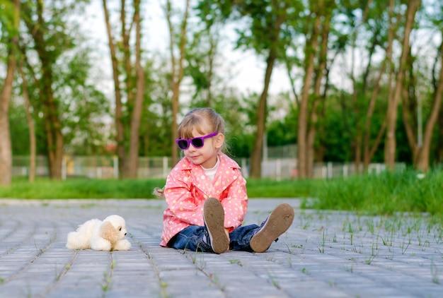 Mała 4-letnia dziewczynka w różowej kurtce i okularach przeciwsłonecznych siedzi samotnie na kamiennej drodze obok małego pluszowego pieska