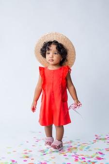 Mała afroamerykanka w czerwonych letnich ubraniach i słomkowym kapeluszu na białym tle w studio
