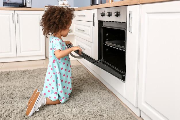 Mała afroamerykańska dziewczyna bawi się piekarnikiem w kuchni. dziecko w niebezpieczeństwie