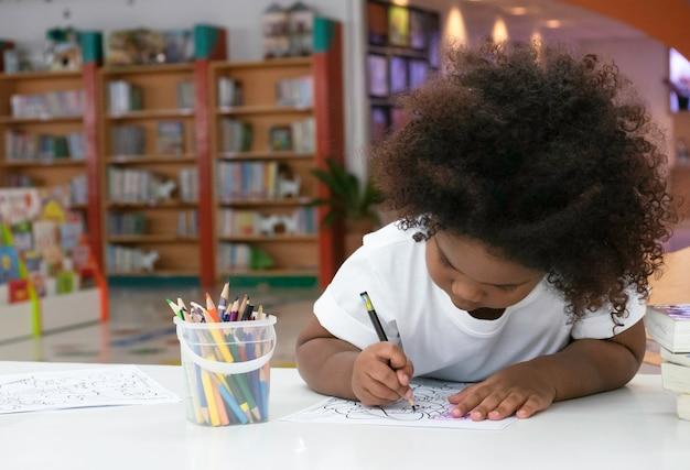 Mała afrykańska dziewczyna maluje i rysuje z szczęściem.