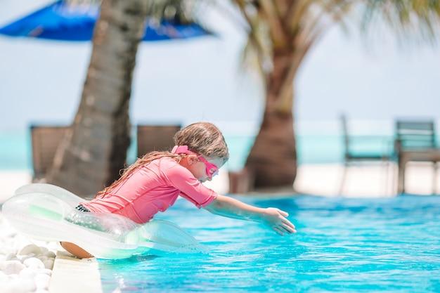 Mała aktywna urocza dziewczyna w plenerowym basenie przygotowywającym pływać