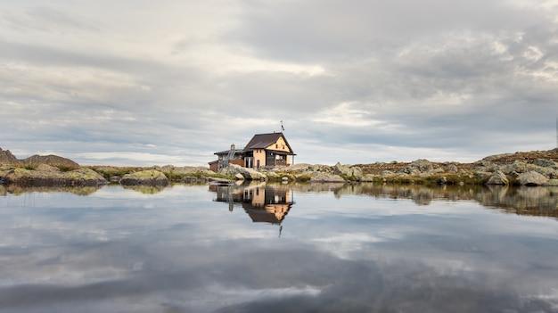 Mała alpejska chata odzwierciedlona w górskim jeziorze