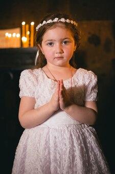 Mała armeńska rudowłosa dziewczyna w starożytnym klasztorze ormiańskim, modląc się i patrząc na kamery przed świecami. religia i duchowość