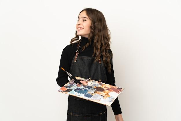 Mała artystka kobieta trzyma paletę na białym tle na białej ścianie, patrząc z boku i uśmiechnięta