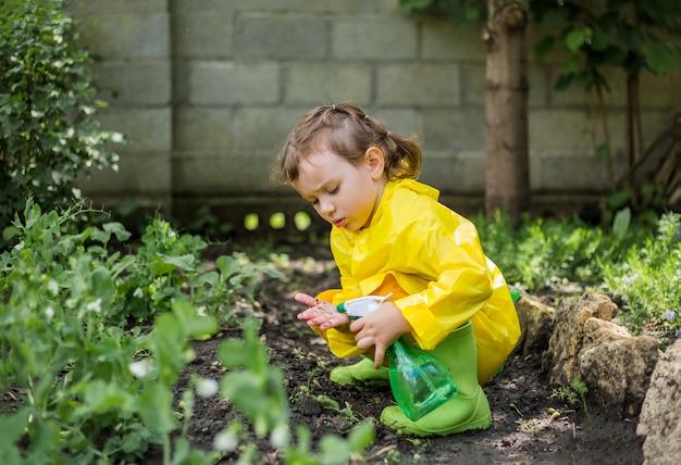 Mała asystentka w żółtym płaszczu przeciwdeszczowym i zielonych gumowych butach pomaga podlewać rośliny w ogrodzie