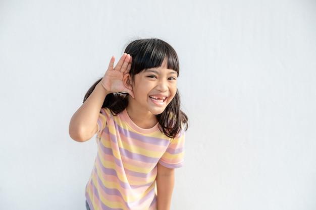 Mała azjatka trzyma rękę w pobliżu ucha i słucha. dzień niepełnosprawności. głuchy dzieciak. ekscytująca twarz na azjatyckiej dziewczynce. wyłączanie telefonu i słuchanie dziecka.