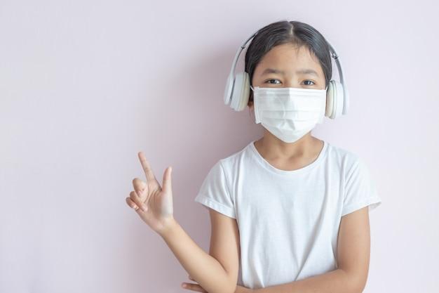 Mała azjatka ubrana w medyczną maskę ochronną i słuchawki