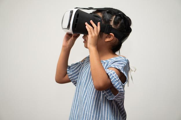 Mała azjatka z zestawem słuchawkowym do wirtualnej rzeczywistości jest ekscytująca dla nowych doświadczeń