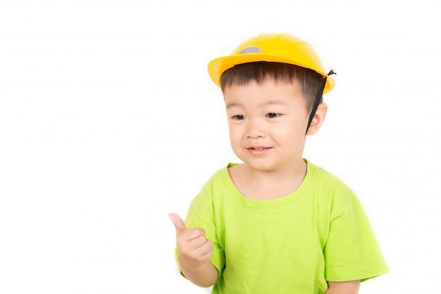 Mała azjatycka berbeć chłopiec bawić się drewnianych bloki jest ubranym hełma inżyniera