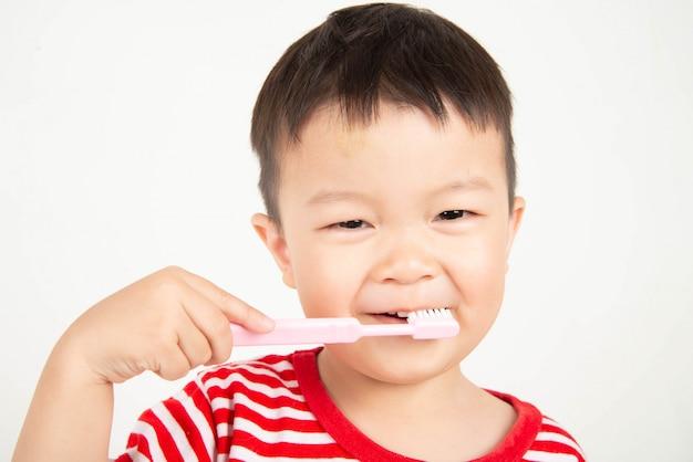 Mała azjatycka berbeć chłopiec szczotkuje zęby