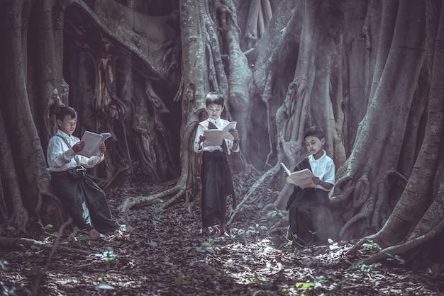 Mała azjatycka chłopiec czyta książkę pod dużym drzewem na obszarach wiejskich