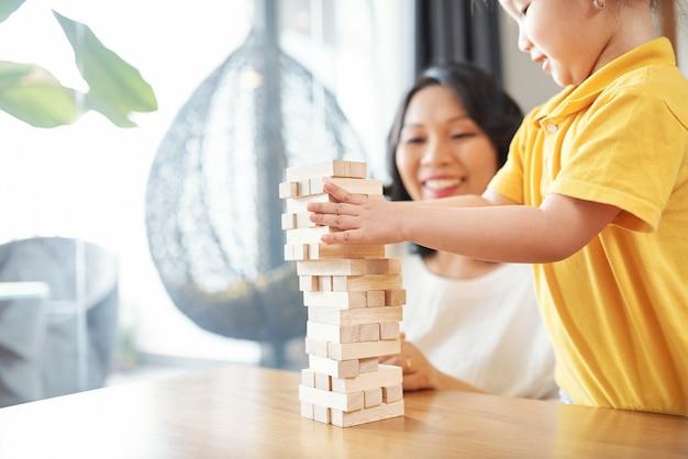 Mała azjatycka dziewczyna i jej matka bawi się drewnianymi cegłami i robi wieżę