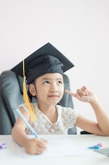 Mała azjatycka dziewczyna jest ubranym absolwenta kapelusz robi pracie domowej