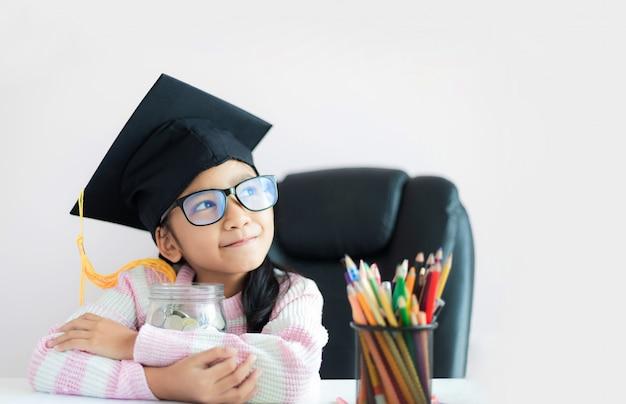 Mała azjatycka dziewczyna jest ubranym absolwenta kapeluszowego przytulenie jasnego szklanego słój