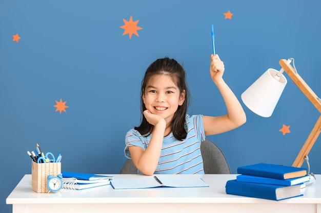 Mała azjatycka dziewczyna robi pracę domową przy stole
