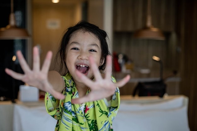 Mała azjatycka dziewczyna uśmiecha się i pokazuje ręce