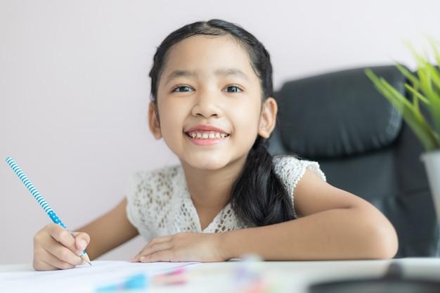 Mała azjatycka dziewczyna używa ołówka do pisania na papierze, odrabiając lekcje