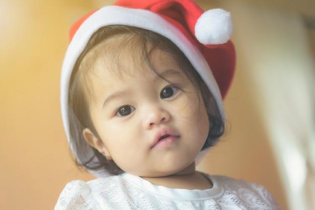 Mała azjatycka dziewczyna w kapeluszu świętego mikołaja. ma ładny i niewinny wygląd.
