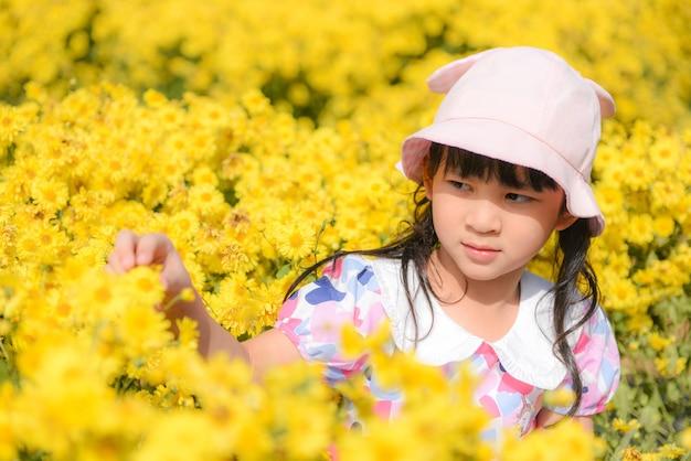 Mała azjatycka dziewczynka dziecko bawić się szczęśliwym porannym ogrodem naturalnym kwitnącymi żółtymi kwiatami