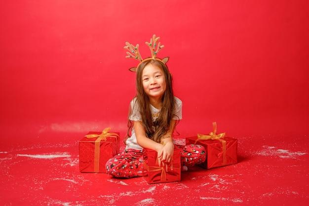 Mała azjatycka dziewczynka w piżamie na czerwonym tle z prezentami