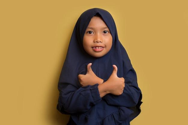 Mała azjatycka muzułmańska hidżab dziewczyna pokazuje kciuki do góry gest