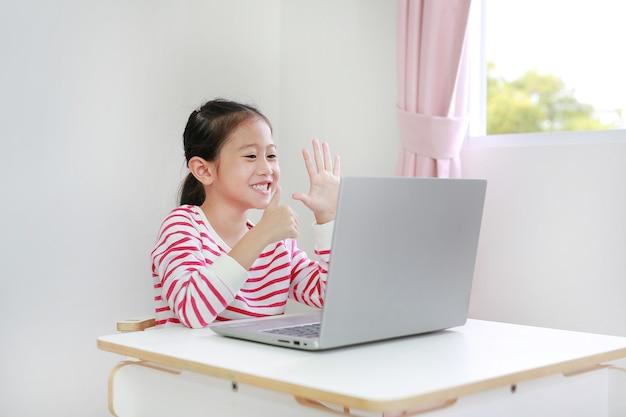 Mała azjatycka uczennica uczy się lekcji online przez połączenie wideo na laptopie