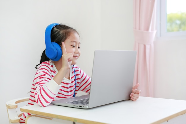 Mała azjatycka uczennica za pomocą słuchawek uczy się lekcji online przez połączenie wideo na laptopie