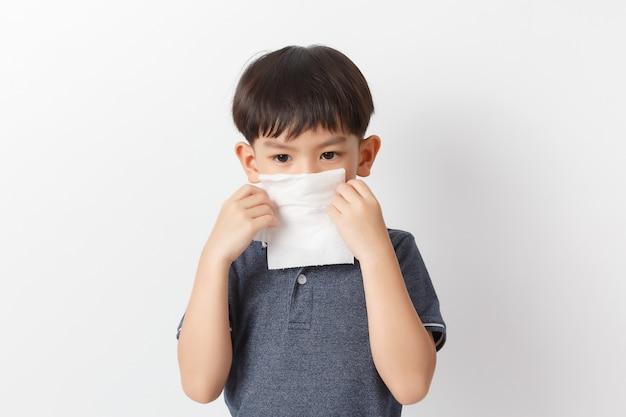 Mała azjatykcia chłopiec trzyma tkankę i dmucha jego nos. dziecko z zimnym nieżytem nosa.