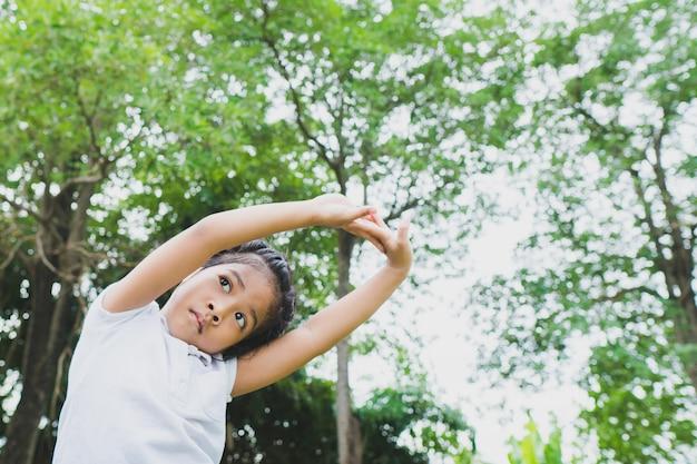 Mała azjatykcia dziecko dziewczyna robi joga w jawnym parku.
