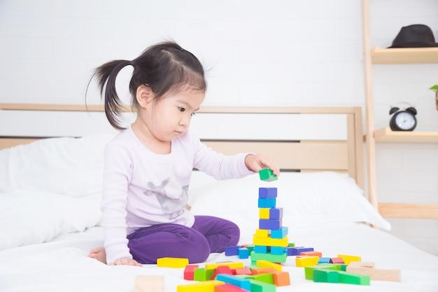 Mała azjatykcia dziewczyna bawić się kolorowych drewnianych bloki na łóżku