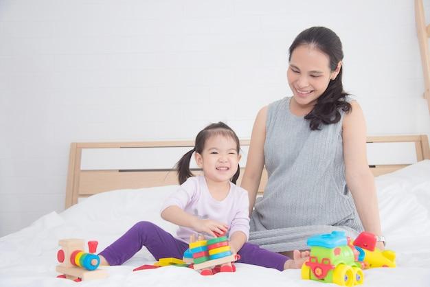 Mała azjatykcia dziewczyna bawić się zabawkę z jej matką