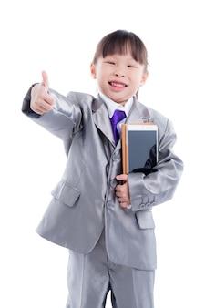 Mała azjatykcia dziewczyna jest ubranym kostium i mienia pastylki komputer uśmiecha się kciuk up i pokazuje