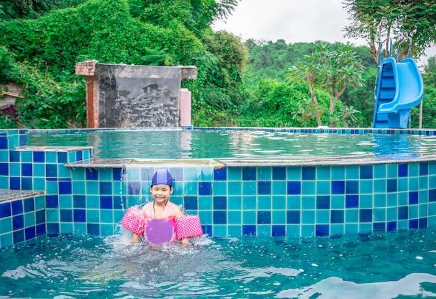 Mała azjatykcia dziewczyna jest ubranym nadmuchiwanych rękawy bawić się w basenie