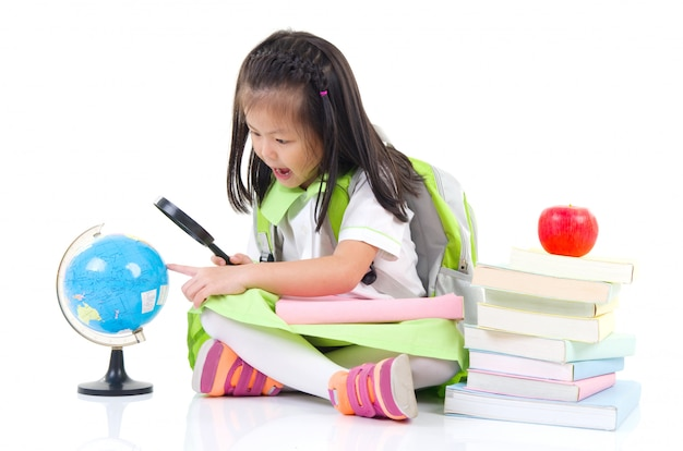 Mała azjatykcia dziewczyna patrzeje przez powiększać - szkło przy kulą ziemską, odizolowywającą na białym tle.