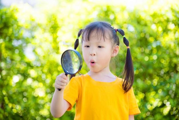 Mała azjatykcia dziewczyna patrzeje przez powiększać z zdziwioną twarzą w parku