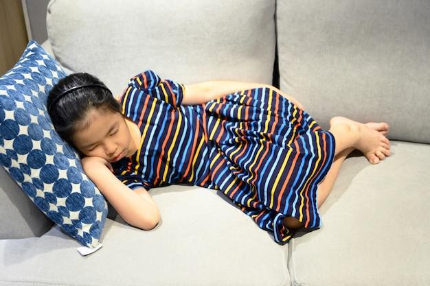 Mała azjatykcia dziewczyna śpi na leżance