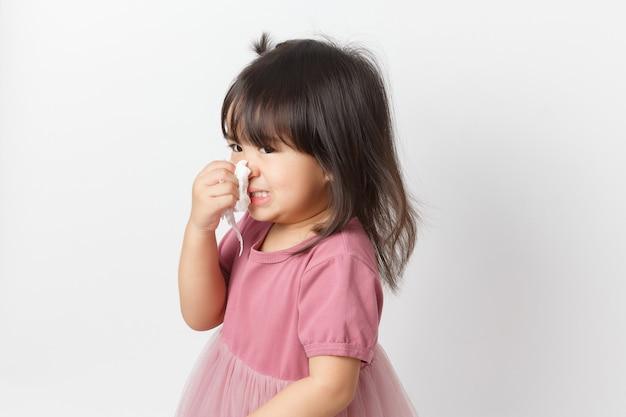 Mała azjatykcia dziewczyna trzyma tkankę i dmucha jej nos. dziecko z zimnym nieżytem nosa.