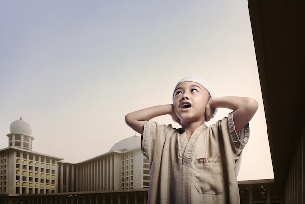 Mała azjatykcia muzułmańska chłopiec jest ubranym nakrętki modlenie
